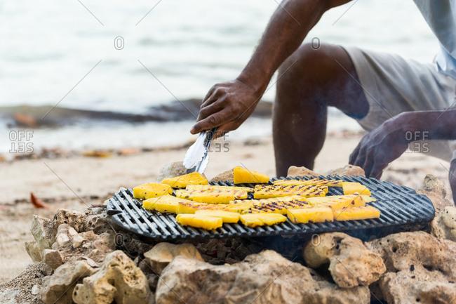 Grilling pineapple on the beach, Vanuatu