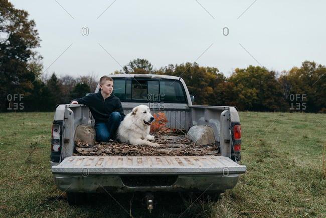 Boy holding his dog in the back of a pickup truck