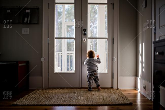 Baby looking out front door