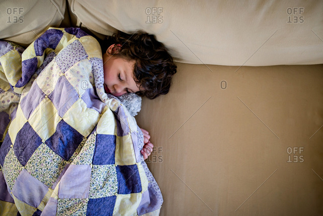 Young boy sleeping under a patchwork quilt