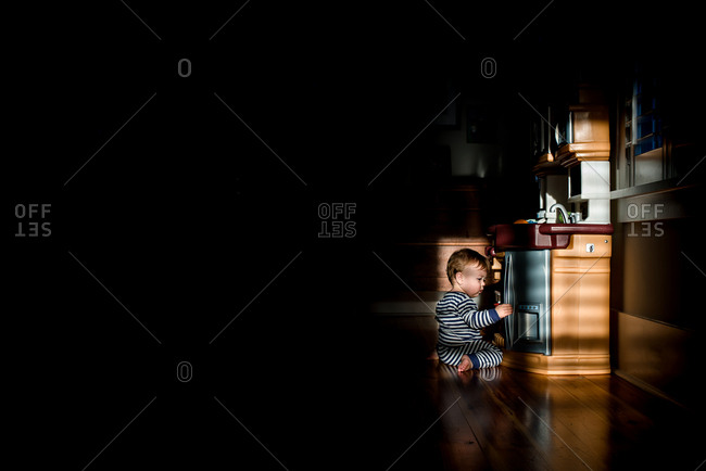 Baby playing with a kitchen play set