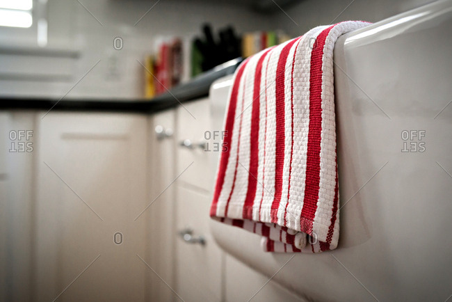 Red and white dish cloth hanging over the kitchen sink