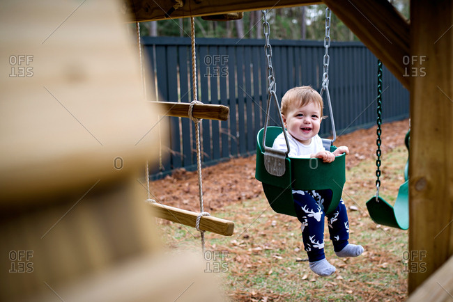 Baby playing on a swing set