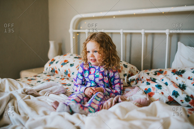Young girl waking up in parents bed
