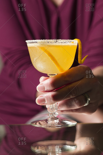 Woman serves a Sidecar cocktail