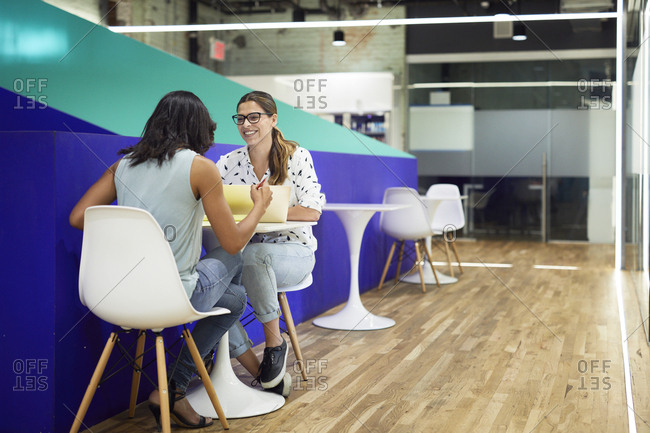 Businesswomen discussing while sitting on chairs at table in cafeteria