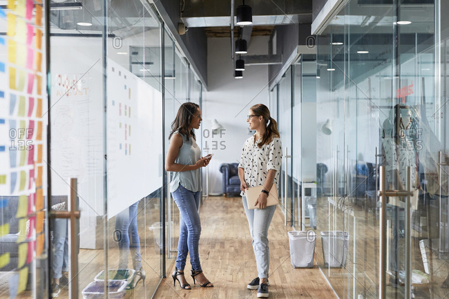 Full length of female business colleagues discussing while standing in corridor