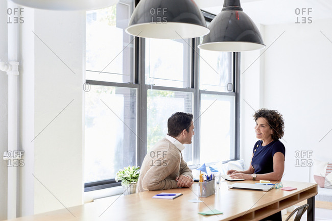 Business colleagues discussing at conference table while sitting by windows at creative office