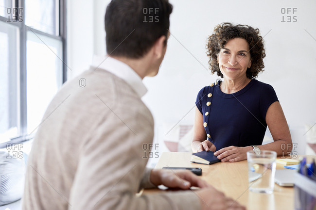 Smiling senior businesswoman discussing with male colleague in meeting at creative office