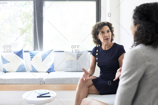 Senior businesswoman discussing with female colleague while sitting on sofa at creative office