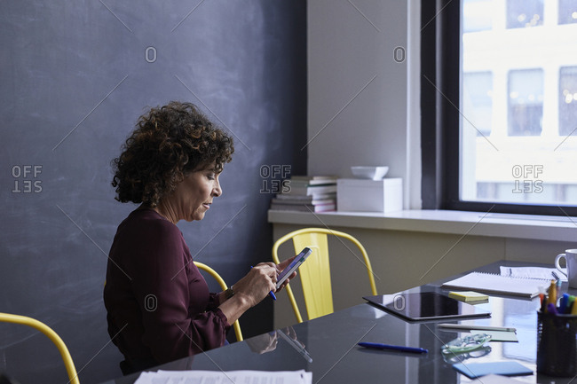 Senior businesswoman using mobile phone while sitting at conference table in creative office