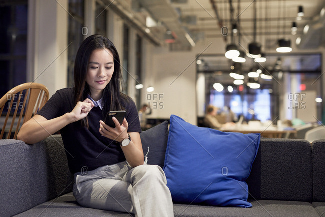 Confident entrepreneur using mobile phone while sitting on sofa at creative office