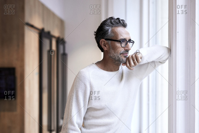 Thoughtful mature businessman standing by window at creative office