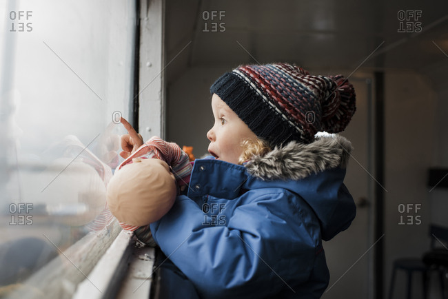 Side view of surprised girl with toy looking through window