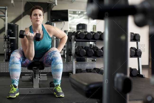 Full length of curvy woman lifting dumbbell while sitting on bench in gym