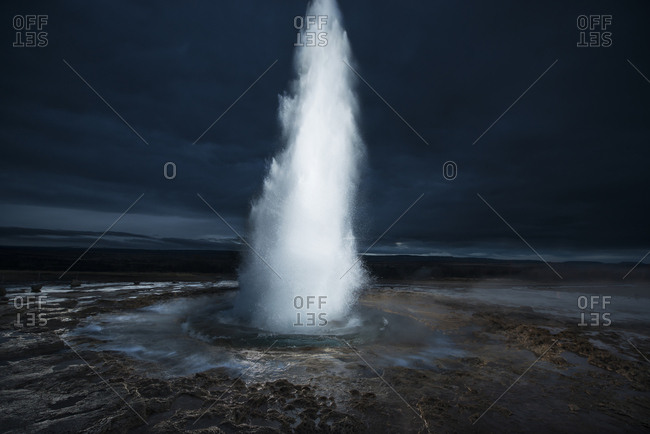 Scenic view of geyser erupting against stormy clouds