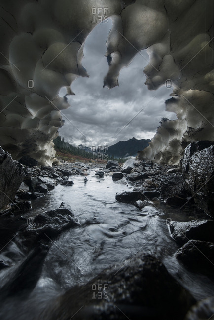 Mountains against cloudy sky seen through ice cave at North Cascades National Park