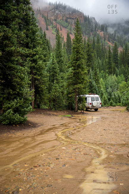 Motor home parked on wet field in forest