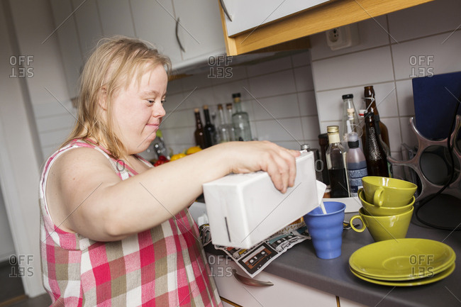 Woman with Down syndrome pouring milk to mug in kitchen