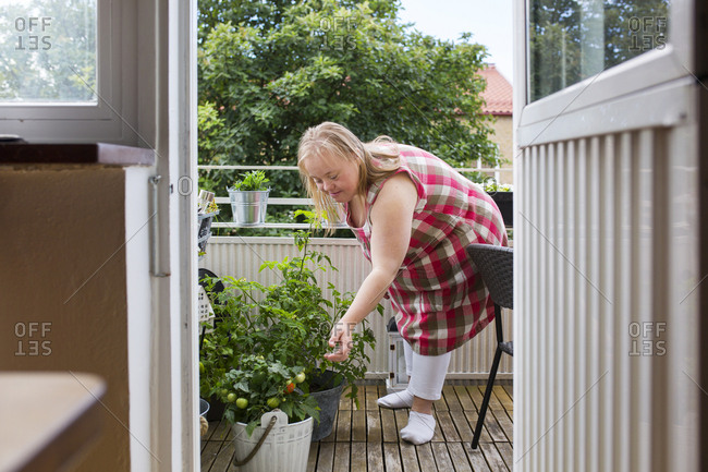Woman with Down syndrome looking at plants on balcony