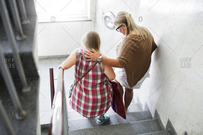 Mother and daughter with Down syndrome walking down stairs