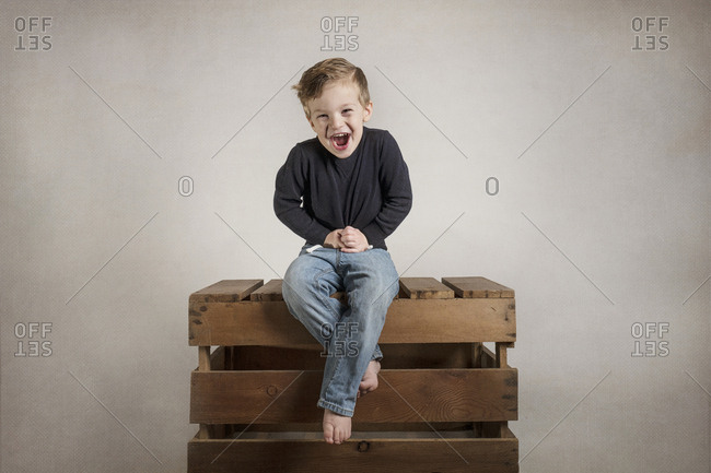 Laughing toddler boy sitting on wooden crate