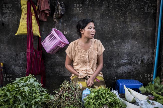 Yangon, Myanmar - September 29, 2016: Woman selling vegetables at a street market in downtown Yangon