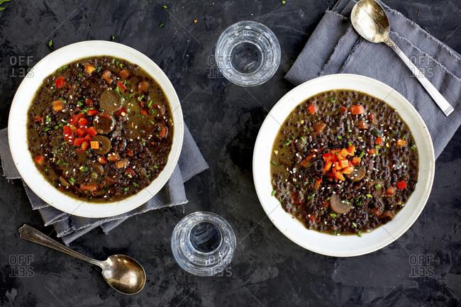 Black Lentil Sesame Coconut Soup served with sparkling water