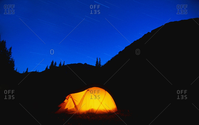 Glowing tent with star trails in the mountains