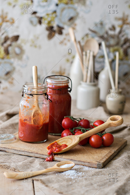 Tomato sauce in jars on a wooden board