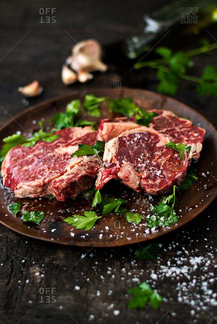 Raw steak seasoned with salt and parsley