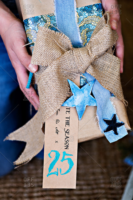 Person holding gift wrapped with jean and burlap ribbons