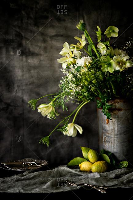 Flowers in a rusty bucket and lemons