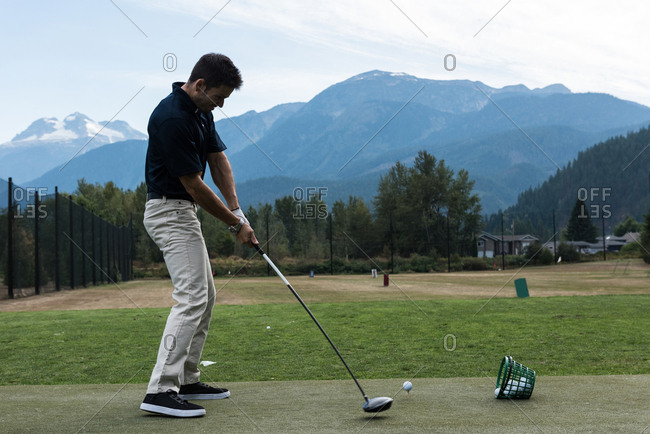 Man performing a golf swing in the golf course
