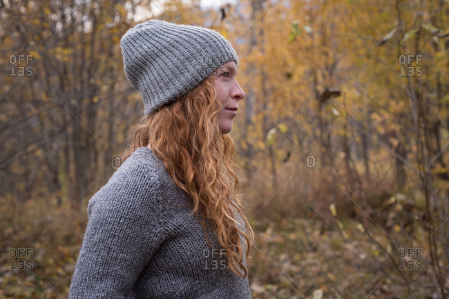 Beautiful woman in warm clothing standing in the autumn forest