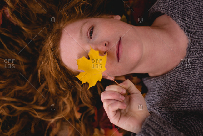 Beautiful woman lying down and holding a maple leaf