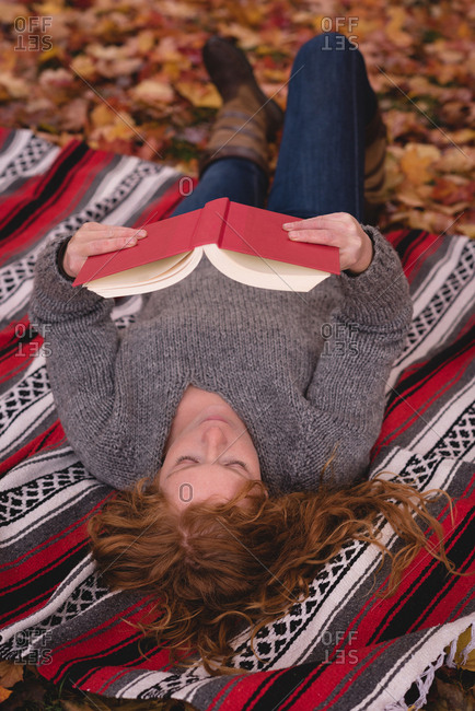 Beautiful woman lying down in the autumn park and reading novel