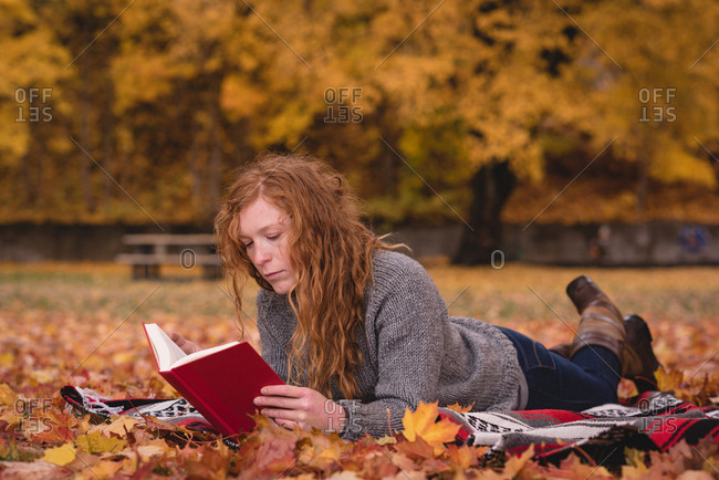 Beautiful woman lying in the autumn park and reading novel