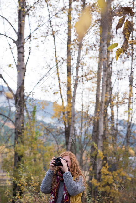 Beautiful woman taking picture of autumn forest with digital camera