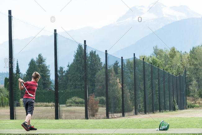 Boy hitting golf shot in the golf course
