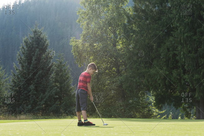 Boy playing golf in the course