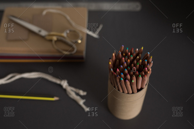 Close-up of colorful pencils in holder at table