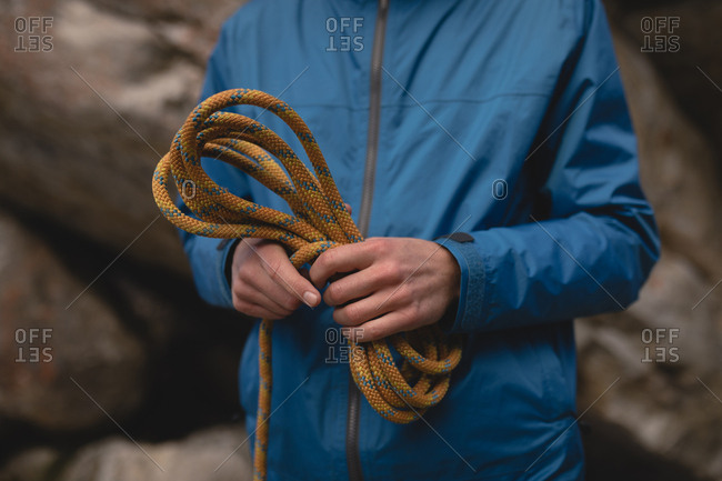 Close-up of hands of hiker folding climbing rope
