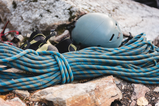 Close-up of rope, helmet and jacket on rock