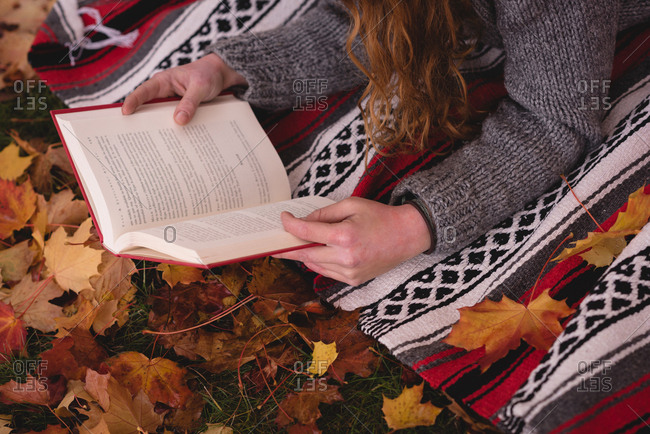 Close-up of woman lying in the autumn park and reading novel