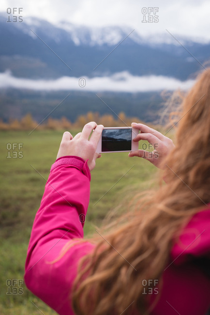 Close-up of woman photographing snow-capped mountains and landscape