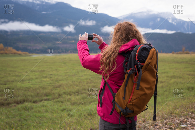 Close-up of woman with backpack photographing snow-capped mountains