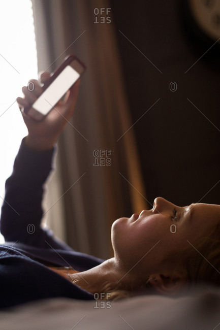 Close-up of young woman lying down on bed using her mobile phone