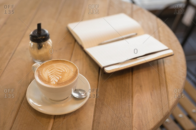 Cup of cappuccino with diary on table in coffee shop
