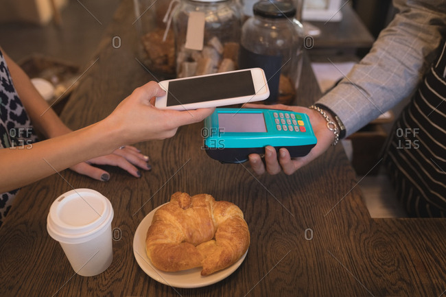Customer making a mobile payment at counter in coffee shop